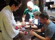 和紙を使って折り鶴を体験する外国人客(松本市中心街で)