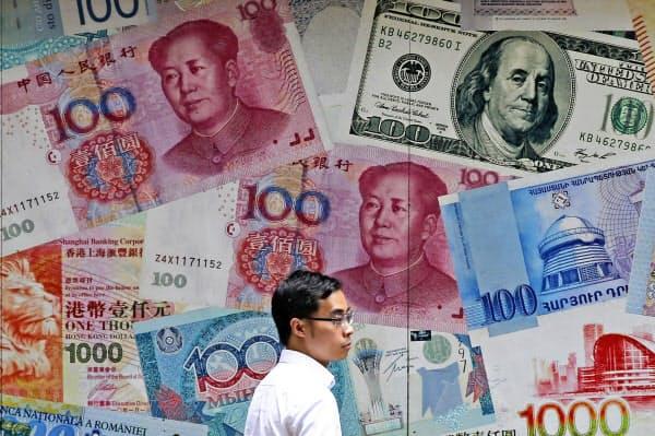 中国・人民元など紙幣イメージが掛かる香港の外貨両替店=AP