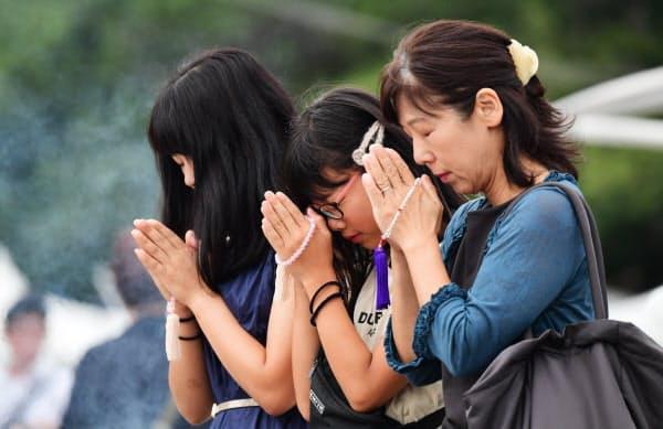 原爆慰霊碑に向かい手を合わせる人たち(6日午前、広島市中区の平和記念公園)