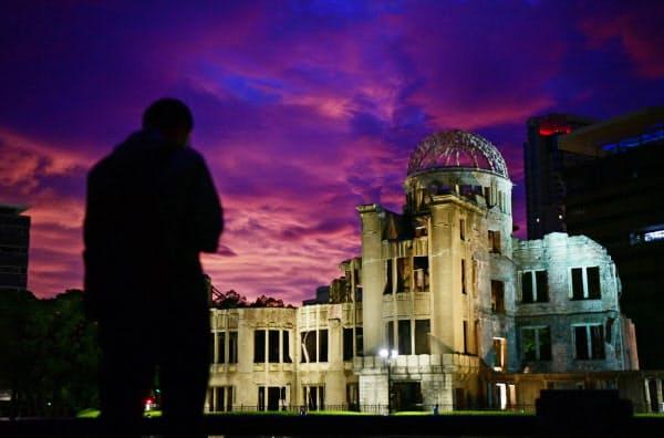 原爆ドームに向かって手を合わせる男性(6日午前、広島市中区の平和記念公園)=目良友樹撮影