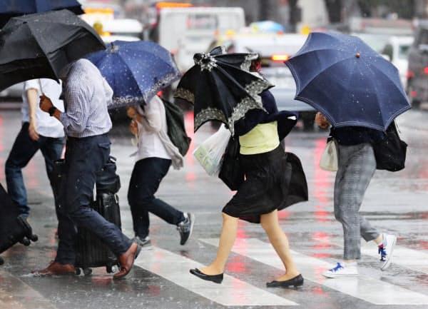 台風8号の影響で雨風が強まり、傘を傾けて歩く人たち(6日午前、福岡市博多区)