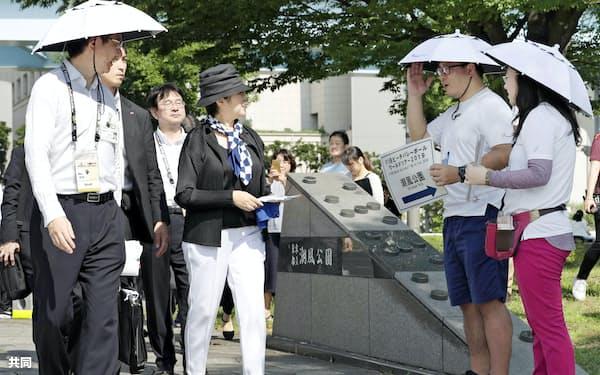 傘をかぶって活動するボランティア(右の2人)を視察する東京都の小池百合子知事(手前左から2人目)=共同