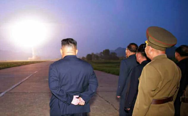 6日のミサイル発射を視察する金正恩委員長(左)=労働新聞ウェブサイトから