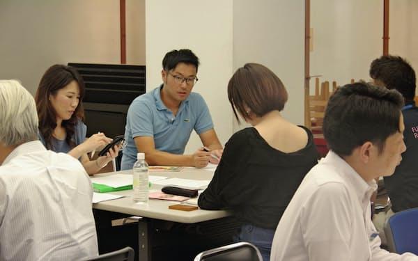 「美めぐり ふくい」の会合で参加者と議論する竹本祐司さん(中)(福井市内)