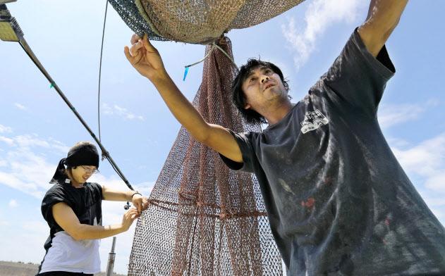 息子の悠成さん(左)の網の補修を手伝う茂呂居諭さん(山口県光市)=沢井慎也撮影