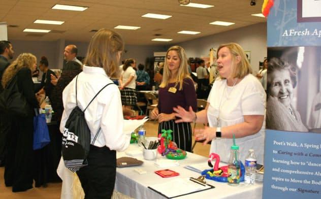 米バージニア州ラウドン郡で開催された就職フェアでリクルーターの説明を聞く求職者