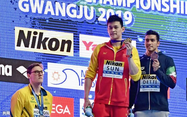 男子400メートル自由形の表彰式。金メダルを手にする孫楊(中央)と表彰台に上がらず抗議の意志を示すオーストラリアのホートン(左)=共同