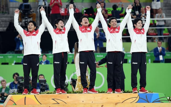 体操男子団体で優勝し表彰台で手を取り合って喜ぶ(左から)山室、内村、田中、白井、加藤