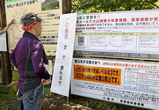 登山道の入り口で浅間山の噴火警戒レベルが3になったことを伝える看板を見る男性=8日午前、長野県小諸市(共同)