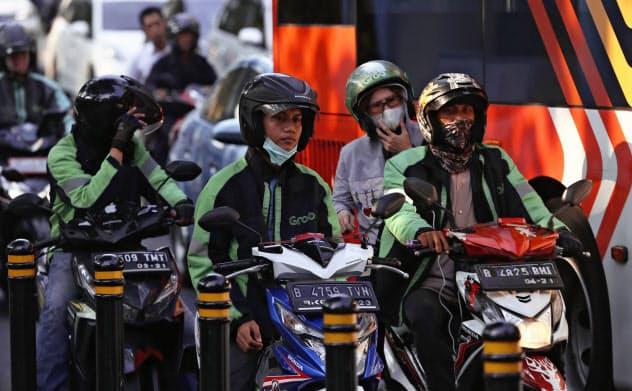 ホンダとヤマハ発動機はインドネシアのバイク市場を二分する(ジャカルタ中心部で信号待ちをするバイクドライバー)=AP
