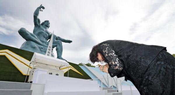 平和祈念像に向かい手を合わせる女性(9日午前、長崎市の平和公園)