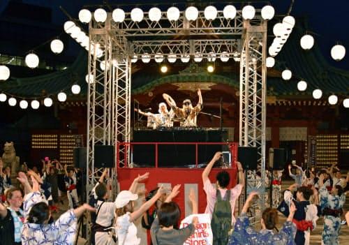 イベント「BON DISCO」で、「DJ KOO」さん(中央右)のダンス音楽で盆踊りを楽しむ人たち(7月、東京・神田明神)=共同