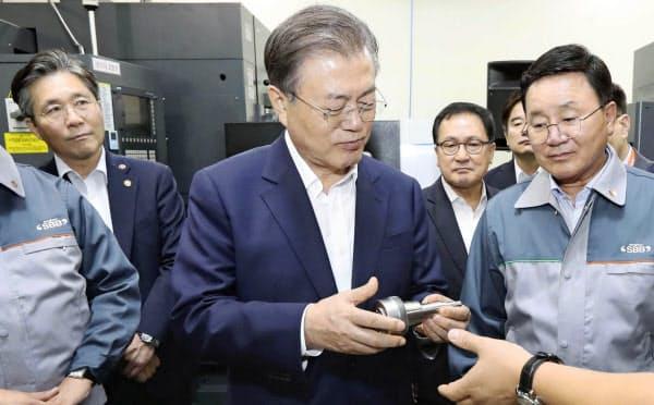 7日、ソウル近郊のロボットに使われる部品などを製造する企業を視察する韓国の文在寅大統領(中央)=聯合・共同