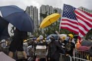 香港のデモでは米国国旗を持つ参加者も目立つ=AP