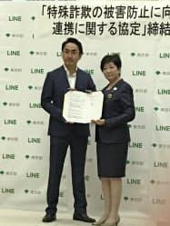 LINEとの協定書にサインした東京都の小池百合子知事(写真右、9日)
