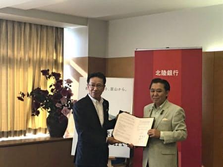 協定書に署名した北陸銀の庵頭取(左)と富山市の森市長(9日、富山市)