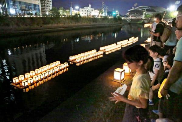 浦上川で平和を願い流された灯籠(9日夕、長崎市)=共同