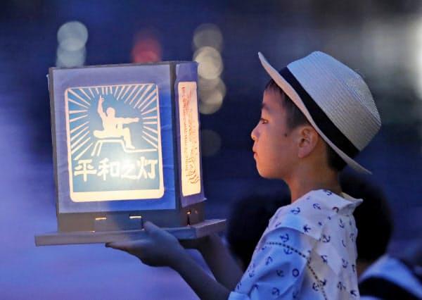 平和を願い浦上川へ流す灯籠を見つめる子ども(9日夕、長崎市)=共同