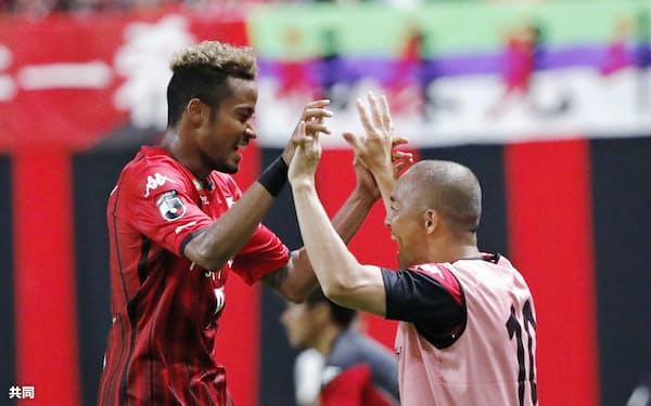 札幌―浦和 後半、同点ゴールを決め、小野(右)と喜ぶ札幌・鈴木(10日、札幌ドーム)=共同