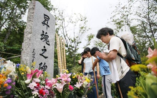 犠牲者の冥福を祈り「昇魂之碑」に手を合わせる遺族ら(12日、群馬県上野村)