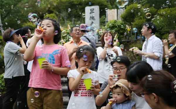 犠牲者の冥福と空の安全を祈り、シャボン玉を飛ばす子供たち(12日、群馬県上野村)
