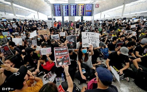 12日、香港国際空港で座り込みをする若者ら=ロイター