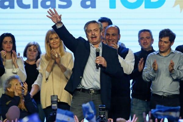 11日夜、ブエノスアイレスの集会で勝利宣言するアルベルト・フェルナンデス元首相(写真中央)=ロイター