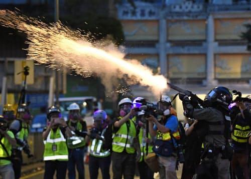 香港中心部で、デモ隊に向け催涙弾を発射する警官隊(11日)=共同