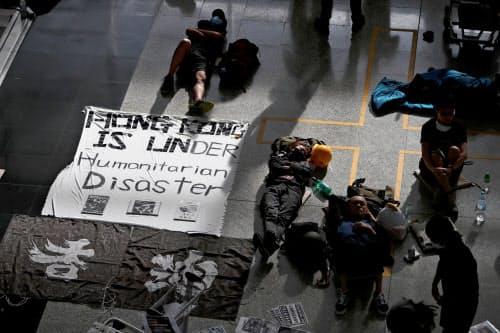 13日、香港国際空港で横たわるデモ隊=ロイター