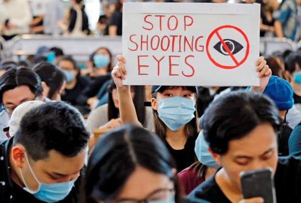 12日、香港国際空港で「目を撃つのをやめて」と書かれたボードを掲げる女性=ロイター