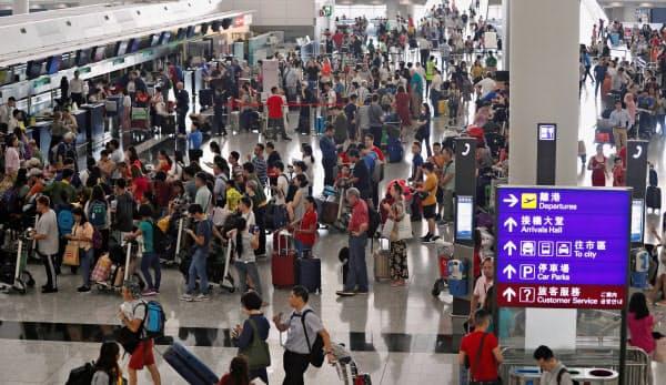 13日、香港国際空港で列を作る乗客=ロイター