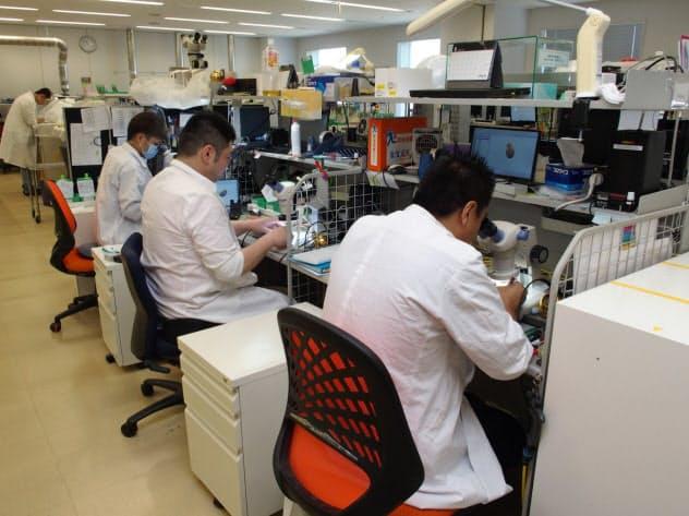 補聴器の製造工程では顕微鏡をのぞきながらの作業も(川崎市)