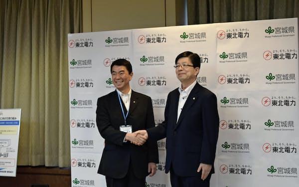 握手を交わす宮城県の村井嘉浩知事(左)と東北電の原田宏哉社長(8日、仙台市)