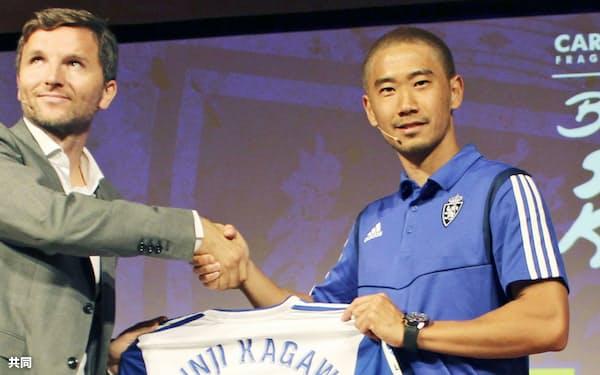 スペイン2部リーグのサラゴサに移籍加入し、チーム関係者(左)と握手する香川真司(13日、サラゴサ)=共同