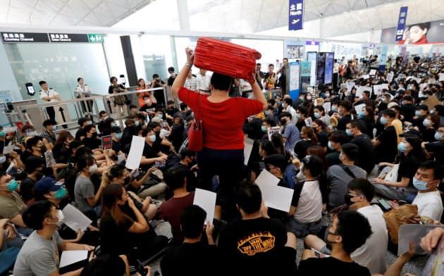 13日、香港国際空港の出発ロビーを埋め尽くす若者ら=ロイター