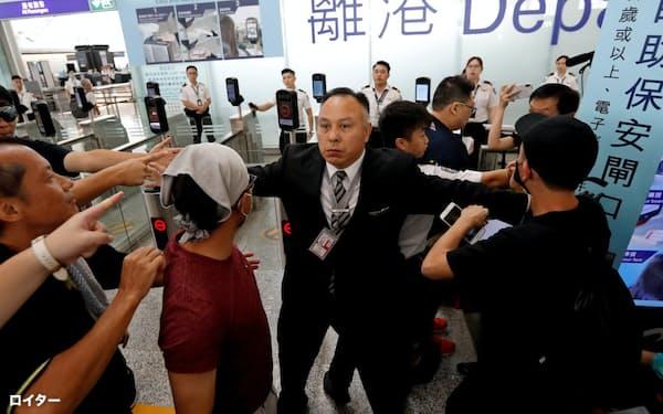 13日、香港国際空港の出発ゲート前でデモ参加者を制止する空港職員=ロイター