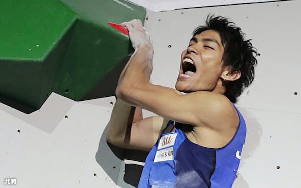 スポーツクライミングの世界選手権男子ボルダリング決勝で、第3課題を完登し雄たけびを上げる楢崎智亜。2大会ぶり2度目の優勝を果たした(13日、東京都八王子市のエスフォルタアリーナ八王子)=共同