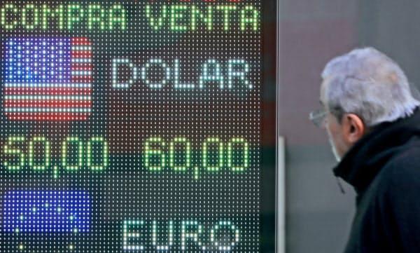 通貨ペソが大幅下落する中、両替商の店頭でレートを確認する男性(12日、ブエノスアイレス)=ロイター