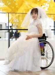 車いすの人も簡単に着られるウエディングドレスのショーに出演した女性(5月、札幌市)=共同