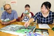 八郎湖の環境問題を学べるカードゲーム「はちリバ」で遊ぶ磯村紋加さん(中央)ら(6日、秋田市)=共同