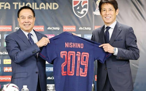 タイ代表監督に就任し、ユニホームを手にポーズをとる西野朗氏。左はタイ・サッカー協会のソムヨット会長(7月19日)=共同