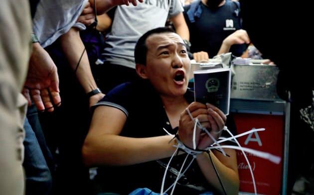デモ隊の一部に拘束された中国共産党系の環球時報の記者(13日、香港国際空港)=ロイター