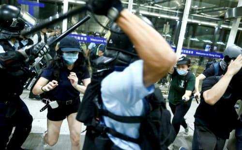 香港国際空港で衝突する警察とデモ隊(13日)=ロイター