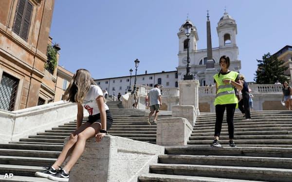 7日、ローマのスペイン階段に座る少女に座らないよう注意する警察官(右)=AP