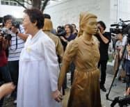 元慰安婦の女性(左)と新設された少女像(14日、ソウル)