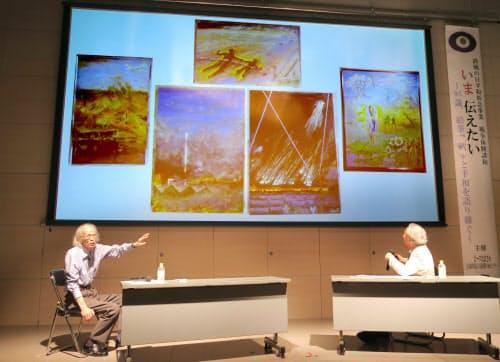 描いた空襲体験画のスライドを前に講演する東村禎三さん(左)(大阪市中央区のピースおおさか)