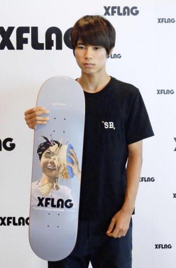 自らの顔がデザインされたスケートボードを手に撮影に応じる堀米雄斗(14日、東京都内)=共同