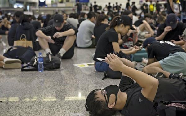 デモ参加者はSNSのやり取りで行動を決める(香港国際空港でスマホを見る若者)=AP