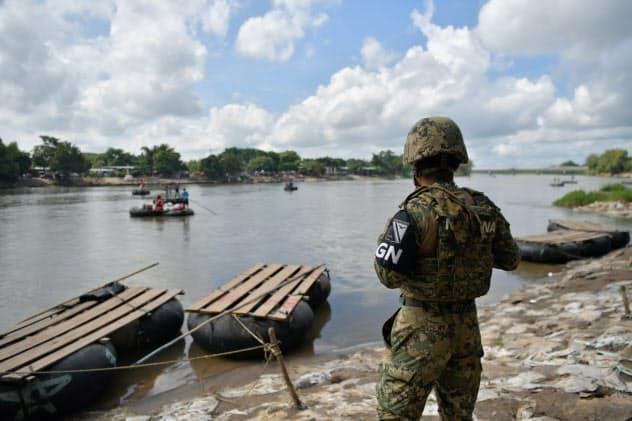 グアテマラからの渡し舟を監視するメキシコ軍の兵士(9日、メキシコ南部タパチュラ)