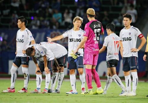 甲府に敗れ、肩を落とす永井(中央)らFC東京イレブン(14日、中銀スタ)=共同